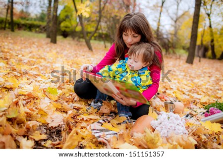 Mom and son reading a book outdoors - stock photo