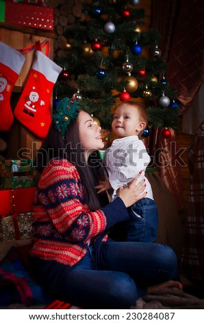 Mom and son sitting under the Christmas tree with gifts - stock photo