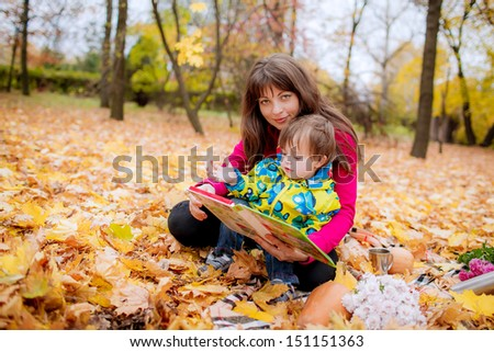 Mom and son 3 years reading a book outdoors - stock photo