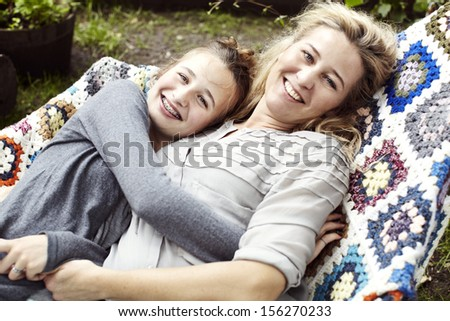 Mom and teenage daughter lying in a hammock - stock photo