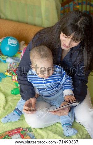 Mom and the little boy reading a book - stock photo
