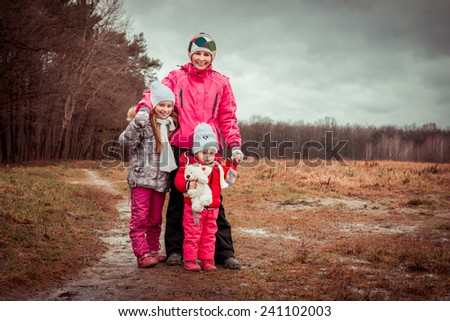 Mom and two her lovely daughters in autumn day - stock photo