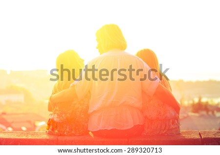 Mom and two sisters twins sitting on the parapet and watch the sunset. Family vintage composition - stock photo