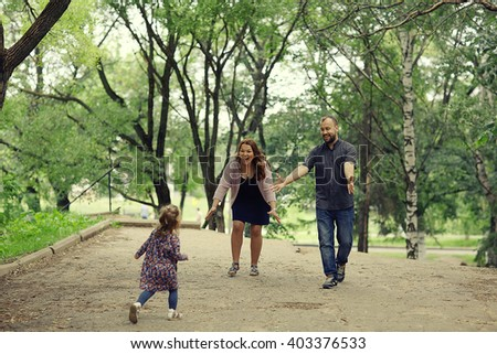 Mom and young daughter and dad, a young family on a walk in the park in summer - stock photo