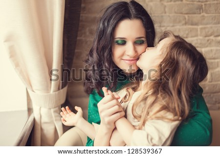 Mom and young daughter eating breakfast - stock photo