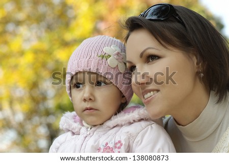 Mom and young daughter  walking in the park in autumn - stock photo