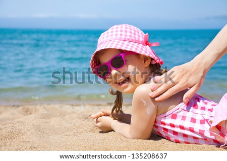 Mom anoints protective cream back a little girl on the beach - stock photo