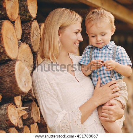 Mom blonde in a white dress holding hands on the little boy, laughing, in the summer at sunset on the background log - stock photo