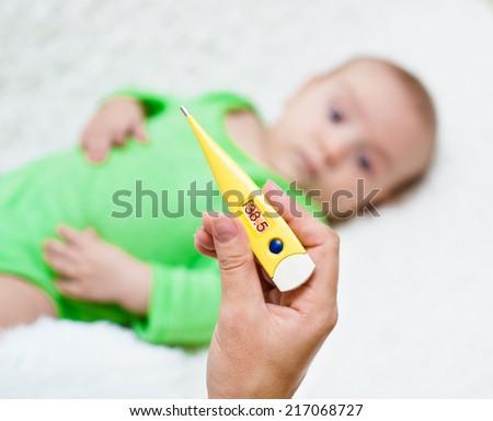 Mom check the temperature of newborn baby - stock photo