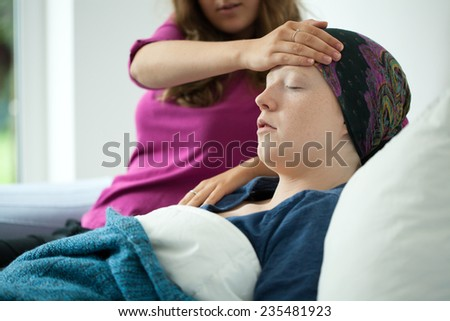 Mom checking the temperature on her sick daughter's forehead - stock photo