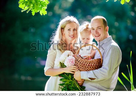 Mom, dad and daughter happy smile on the background of the forest and water in backlight - stock photo