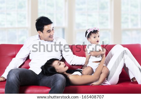 Mom dad and daughter having fun on red sofa at home - stock photo