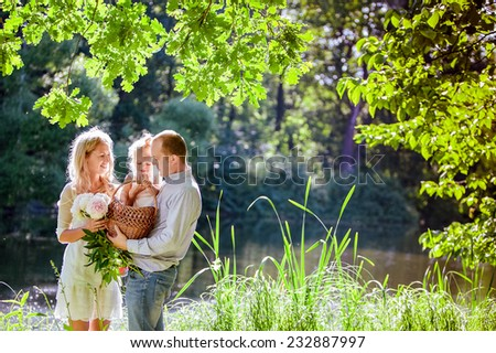 Mom , dad and daughter on the background of the forest and water in backlight - stock photo