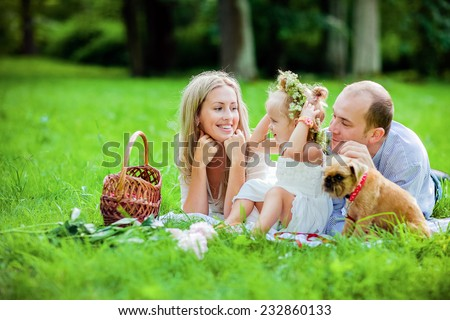 Mom, dad, little girl blonde and dog happy lie together on the grass - stock photo