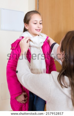 Mom dressing her child in a warm overcoat and scarf - stock photo