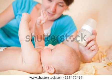 Mom  feed  baby with bottle, play in bed - stock photo
