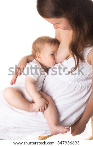 Mom feeds the baby breast, white dress, light background - stock photo