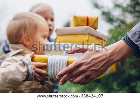 Mom gives gifts to children - stock photo