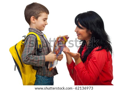 Mom giving explanation to her little son and preparing him for fist day of school,the boy holding bag and  books and looking attentive to his mother - stock photo