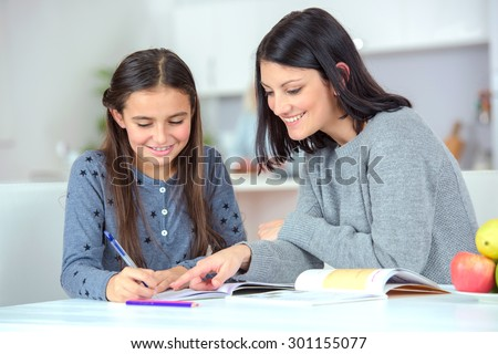 Mom helping her daughter do her homework - stock photo