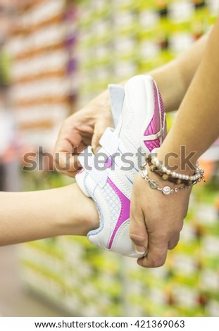 Mom helping toddler fitting with new shoes - stock photo