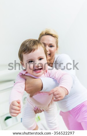 Mom holding baby little girl in front of the camera.Baby smiling at camera.Low angle view, Shallow doff - stock photo