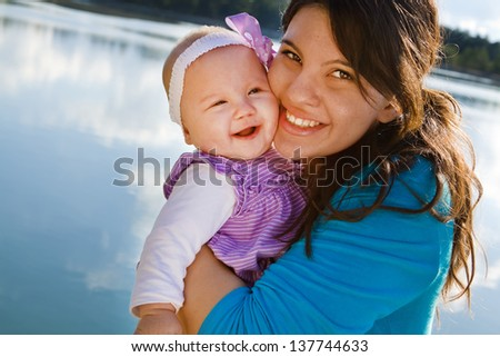 Mom holding smiling baby girl by a lake - stock photo
