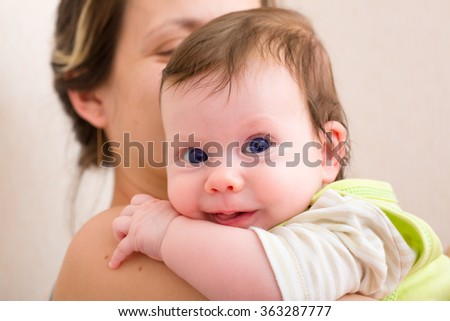 Mom holding the smile baby in her arms - stock photo