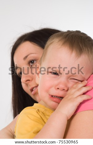 mom holds a crying baby on a white background - stock photo