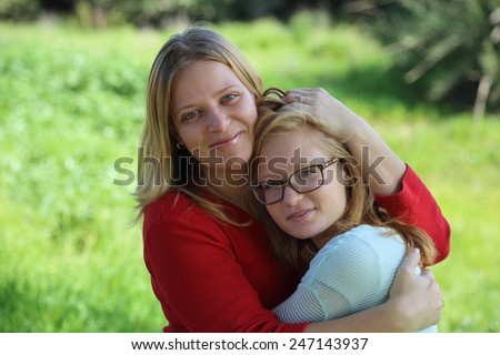 Mom hugging daughter teenager on a background of nature - stock photo