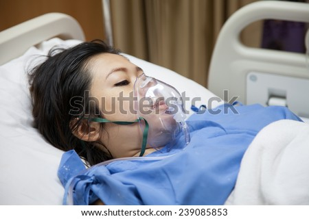 Mom in mask oxygen after childbirth - stock photo