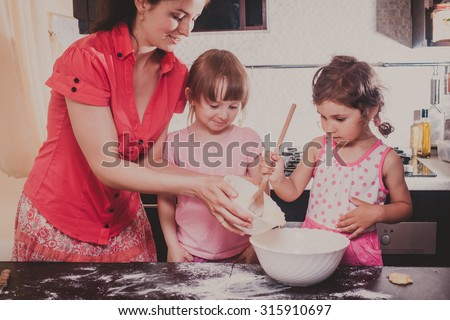 Mom is baking cookies with her kids at home kitchen - stock photo