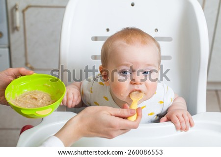 Mom is feeding baby with a spoon - stock photo