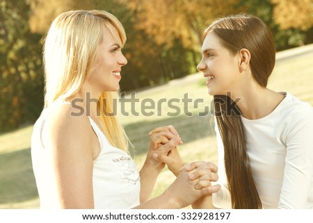 Mom is her friend. Happy beautiful mother and daughter looking at each other smiling holding hands on a nice warm day - stock photo
