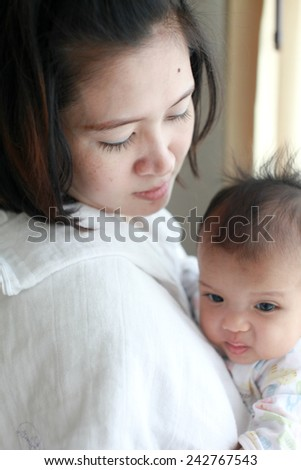 Mom is holding and kissing her baby with love - stock photo
