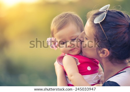 Mom is kissing child on sunshine spring summer day , parent love  - stock photo