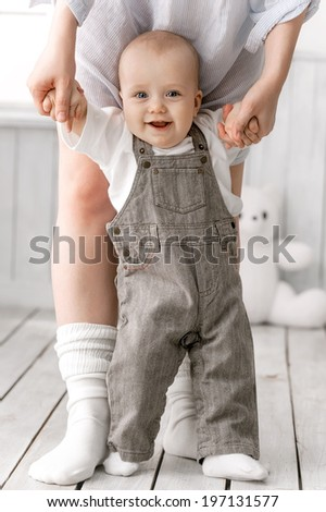 Mom leads a happy kid handles on the floor - stock photo