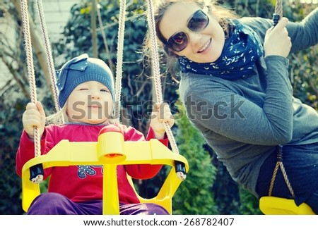 Mom playing with her daughter on a swing in the park. Vintage style. - stock photo