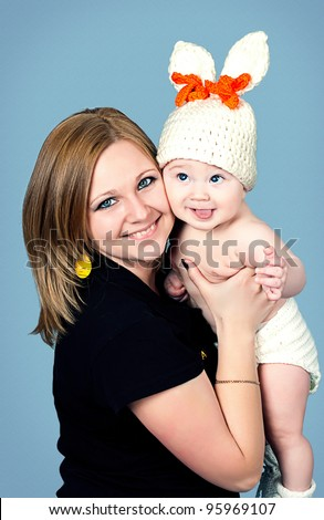 Mom plays with her little son in her arms. Gay kid. - stock photo