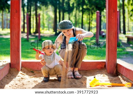 Mom plays with the child in a sandbox - stock photo