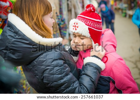 Mom puts a cap on daughter, fitting hats in the store in spring - stock photo