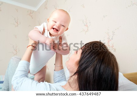Mom raised her hands up baby, baby smiling and laughing. A happy family. - stock photo