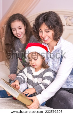 Mom reading a Christmas story with children. Little girl in Santa's hat holding a big book - stock photo