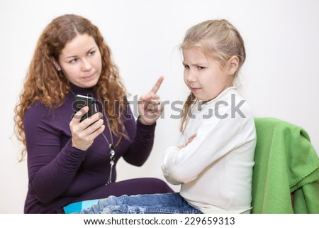Mom scolding a child for viewing inappropriate content on your smartphone - stock photo