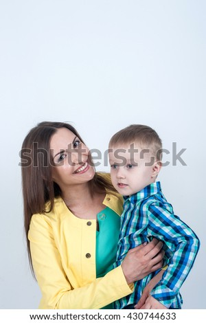Mom smiles tightly hugging her young son - stock photo