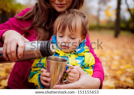 Mom son pours tea from a thermos in the autumn park - stock photo