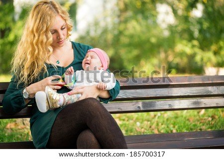 Mom soothes a crying baby, sitting on a park bench  - stock photo