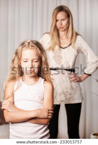 Mom swears by daughter. Conflict, problems in family. Sad mother and child - stock photo