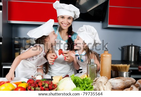 Mom teaches two daughters to cook at the kitchen table with raw food, clothing cooks - stock photo