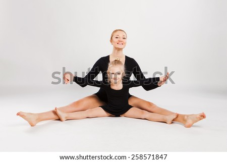 Mom teaching daughter dancing. mother and daughter gymnastics - stock photo